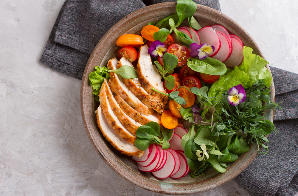 Spring salad with vegetables, chicken breast and edible flowe
